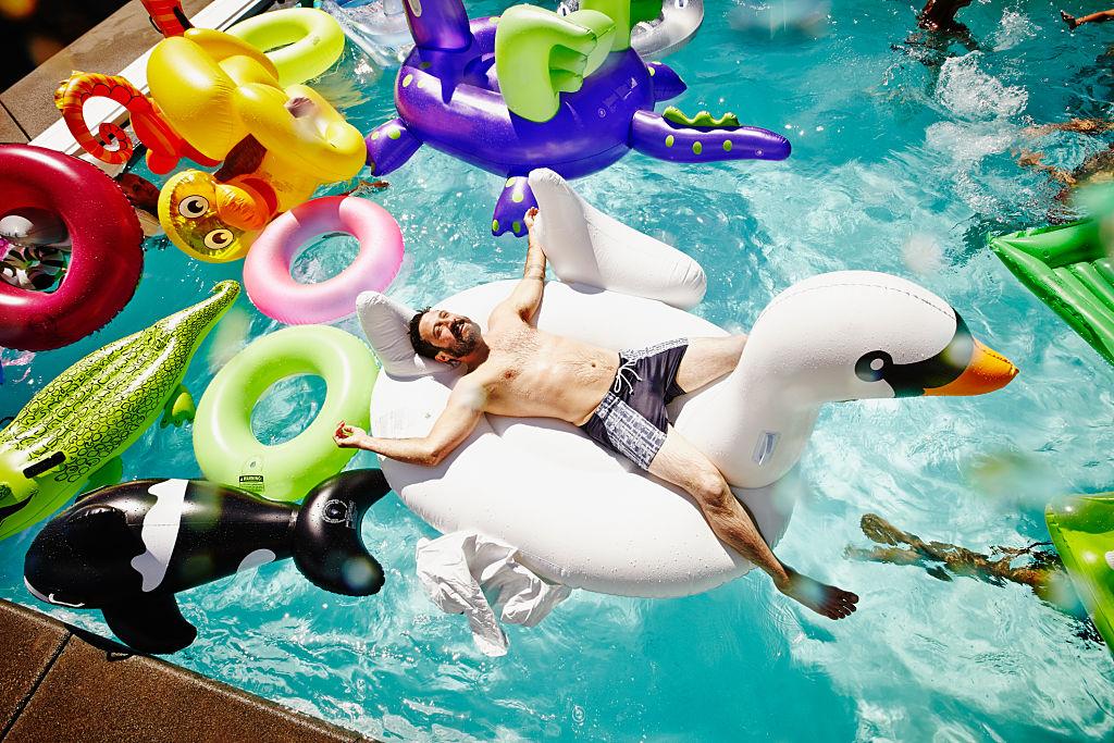 un homme souriant sur un cygne gonflable dans une piscine